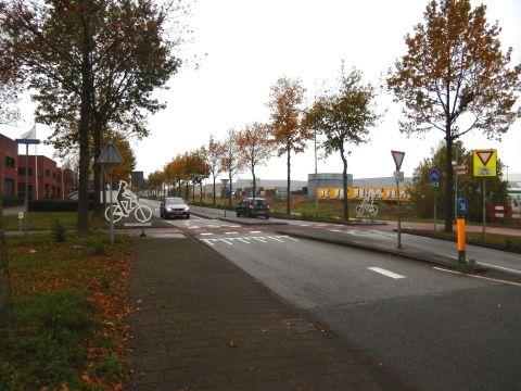 Op deze drukke weg is er bijkomende signalisatie aangebracht. Het fluo stopteken en witte fietsers als aanduiding dat dit een fietsvoorrangsweg is.