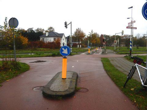 De enige oversteekplaats met verkeerslichten. Hier wordt gewerkt met verwegdetectie. Als de fietser over de detectielijnen rijdt (onderaan de foto) krijgen de verkeerslichten het signaal dat er een fietser op komst is en verspringen dan op groen voor de fietser.